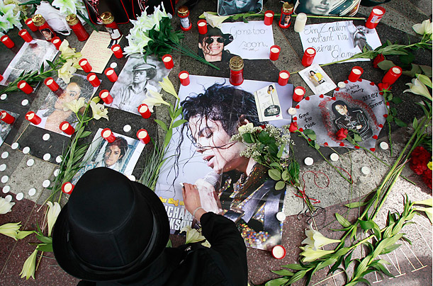 A Michael Jackson fan in Berlin, lights candles to commemorate the death of Jackson one year ago today.