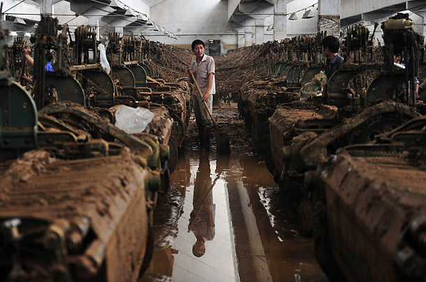 Workers at a textile mill in Nanping, China clean up mud left by a flood.