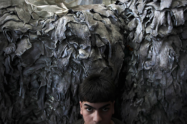 A worker rests next to hides waiting to be processed at a leather factory in Hebron, Israel. After they are processed, the hides will be sold to local shoes factories.