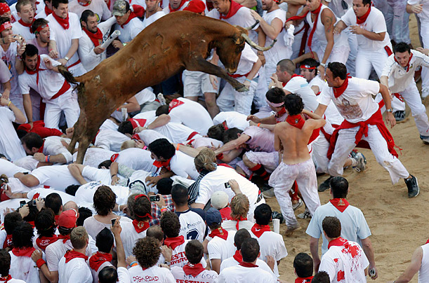 A bull leaps over participants in the first running of the bulls during the second day of the San Fermin festival in Pamplona, Spain.