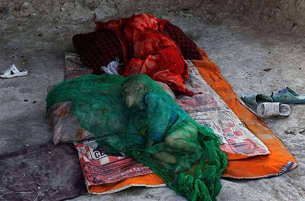 An Afghan child sleeps under netting to protect her from flies at a refugee camp for internally displaced people in Kabul.