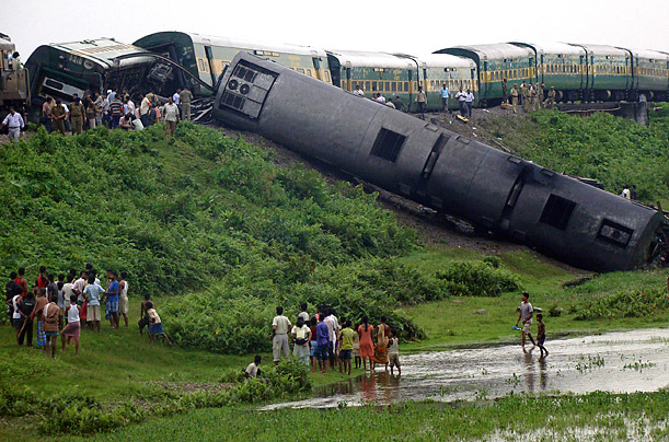 Onlookers and railway officials stand beside a passenger train that derailed after an explosion in Kokrajhar, India.