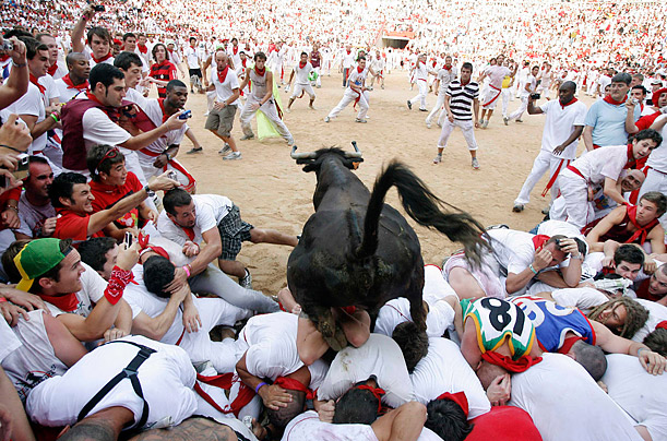 A fighting cow leaps over revellers during bullring festivities after the second running of the bulls at the San Fermin festival in Pamplona, Spain.