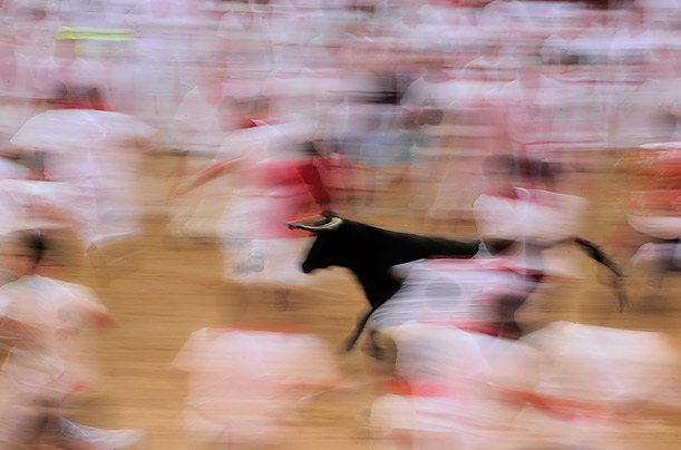 The crowd is a blur while they run from a charging calf during the third running of the bulls in Pamplona, Spain.
