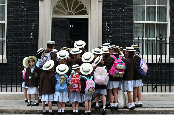 Schoolchildren stand outside the entrance to Number 10 while visiting Downing Street  in London.