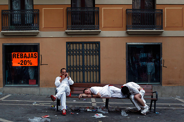 Revellers rest on a bench before the seventh running of the bulls in Pamplona.