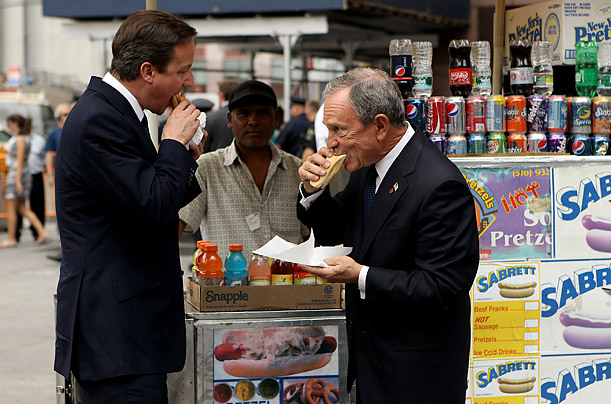 British Prime Minister David Cameron and New York City Mayor Michael Bloomberg eat hot dogs  outside Penn Station in New York.