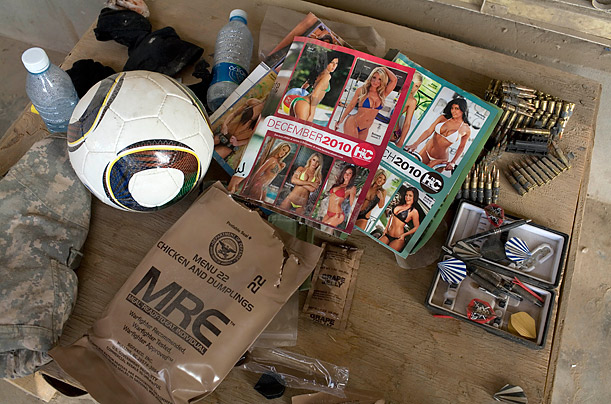 Items including bullets, darts and Hooters calendars lie scattered on a table after mealtime at Combat Outpost Nolen, in Kandahar, Afghanistan.