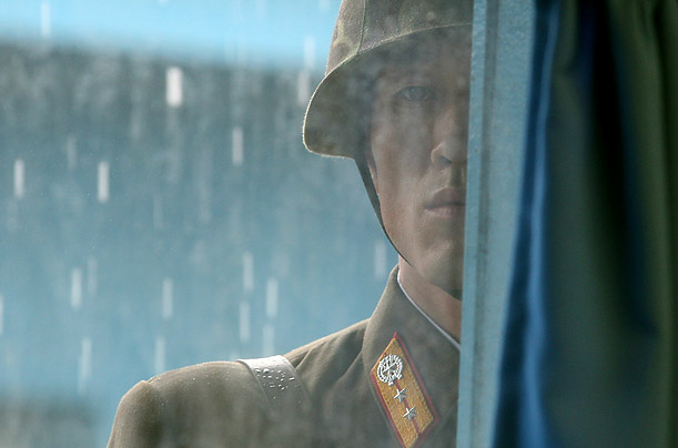 A North Korean soldier looks through the window of the UN truce village building that sits on the border of the Demilitarized Zone (DMZ) during a visit by Secretary of State Hillary Clinton and Secretary of Defense Robert Gates.