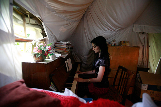 Natalya Dzasokhova plays a piano in a tent, where she lives with her husband Grigory. Their house was destroyed during the Georgia's war with Russia over South Ossetia.