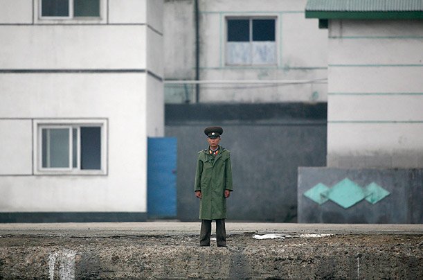 A North Korean soldier stands guard beside the Yalu River near the North Korean town of Sinuiju.