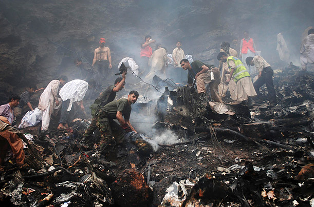 Soldiers, rescue workers and residents search through the wreckage of an Airblue passenger plane which crashed in Islamabad, Pakistan's Margalla Hills.