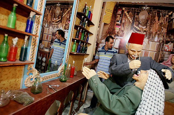 A display of a dentist's office inside a Jenin museum depicting daily Palestinian life is adjusted by a worker affiliated with the museum.