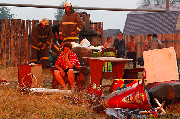 A woman sits among her belongings as she watches her home go up in flames.  Extreme heat has caused numerous forest fires throughout Russia, killing five people and destroying hundreds of homes.