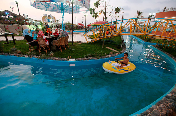 A Palestinian boy rides on a float in a pool at Crazy Water Park in Gaza City.