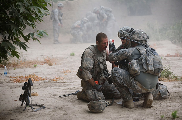 Members of the U.S. Army assist a soldier after he was injured by an improvised mine in the volatile Arghandab Valley of Kandahar, Afghanistan.