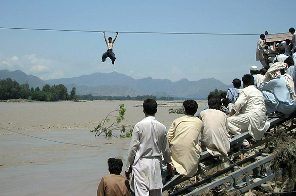 Onlookers watch from a damaged bridge as a Pakistani flood survivor climbs a rope to cross the river in Pakistan's Swat Valley.  Around 3.2 million people have been affected by the torrential monsoon rains hitting Pakistan.
