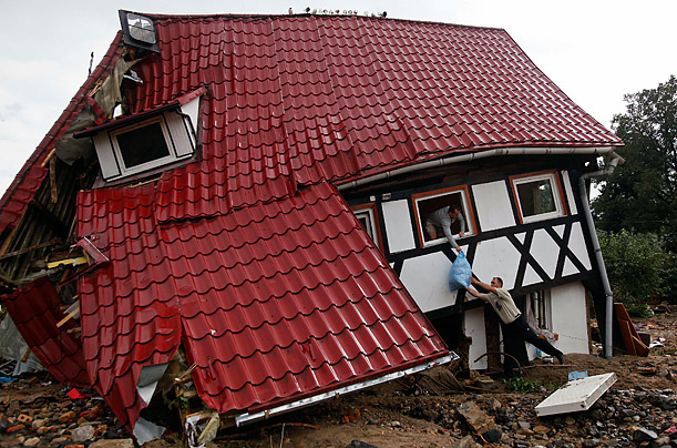 Residents pass a bag out the window of their house in Bogatynia, Poland which was damaged by flash flooding.