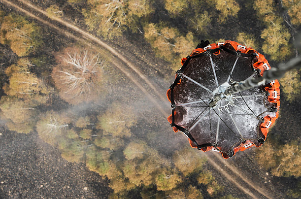 A helicopter carries water before releasing it over a forest fire near Kustarevka, Russia.