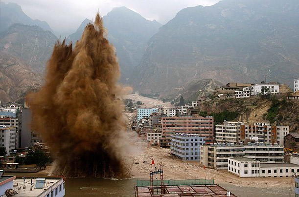 A controlled explosion is used to clear away debris blocking the flow of a river after a mudslide swept into the town of Zhouqu in the Tibetan Autonomous Region.