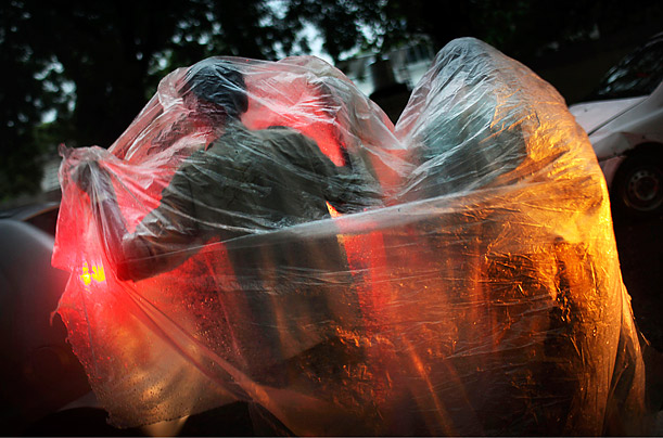 Indian men cover themselves with a plastic sheet as they try to stay dry while walking through traffic during a heavy monsoon in New Delhi, India.