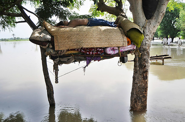 A flood survivor sleeps on a hammock in a flooded area of the village of Shah Jamal village in Pakistan.