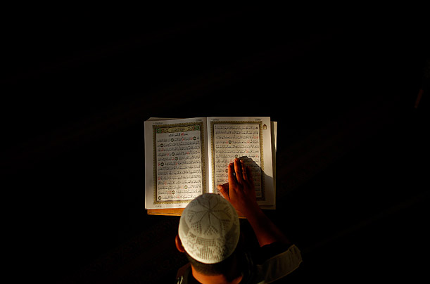 A Palestinian man reads from the Quran during early morning prayers at a Mosque during Ramadan.