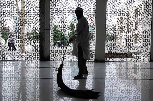 A man cleans the floor of the national mosque in Dhaka, Bangladesh, preparing for afternoon prayers during Ramadan.