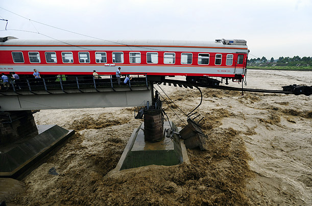 Officials inspect a train atop a collapsed bridge after passengers were evacuated near Guanghan, China.