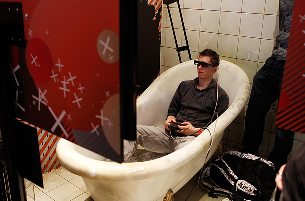 A visitor wearing 3D glasses plays with a PlayStation at Gamescom 2010 in Cologne, Germany.