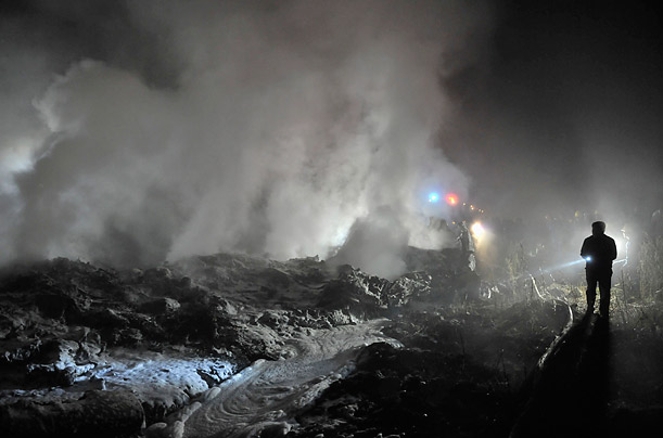 Rescuers check the remains of the Henan Airlines passenger plan that crashed in Yichun, Heilongjiang Province.