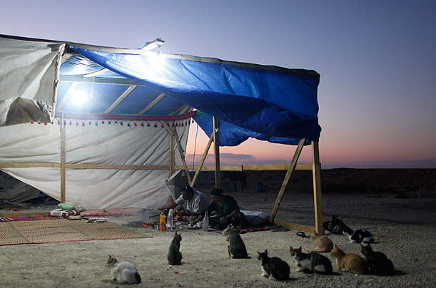 A Bedouin family enjoys an Iftar meal, a traditional meal to break the fast during the holy month of Ramadan, in a Bedouin village near Beersheba, southern Israel.