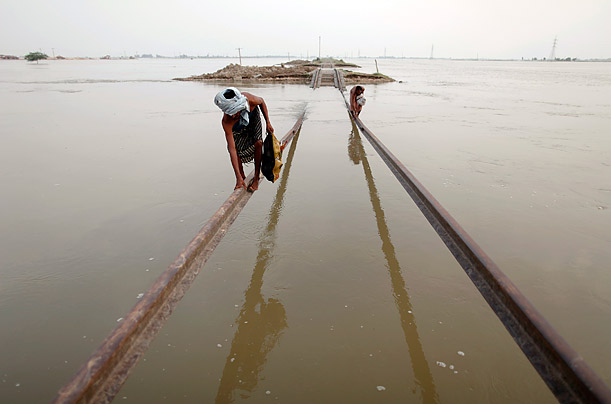 Flood victims use part of a damaged railway track to traverse rising waters in Pakistan's Sindh province.