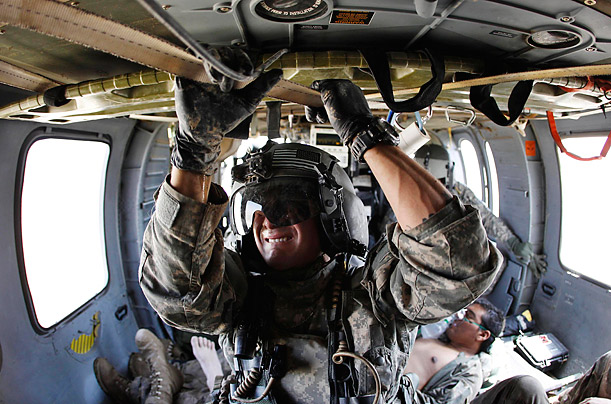 Sergeant Jay Kenney holds on to a support strap in a medevac helicopter carrying a wounded  Afghan soldier.