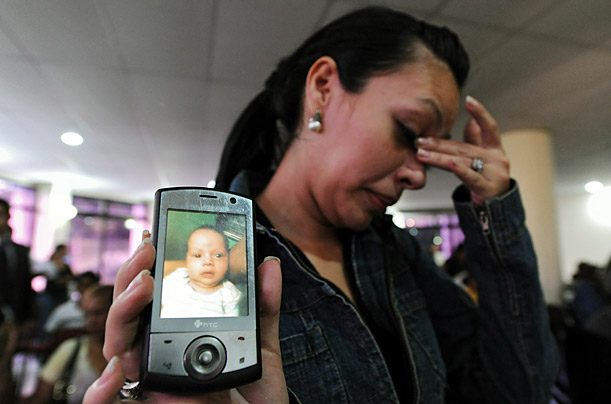 A Honduran woman in Tegucigalpa, Honduras shows the picture of her baby, whose father was among the 72 immigrants murdered in Mexico.
