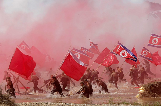 South Korean Army soldiers dressed as North Korean soldiers re-enact  the Naktong River Battle on the 60th anniversary of the Korean War.