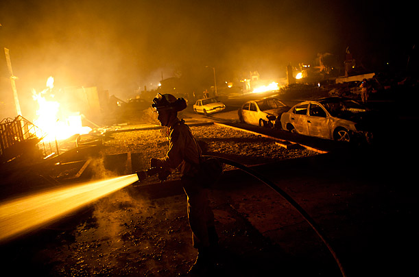 Firefighters work to contain a massive fire that tore through a residential neighborhood in San Bruno, Ca.  A large gas explosion leveled the small residential neighborhood, killing at least 4 residents.