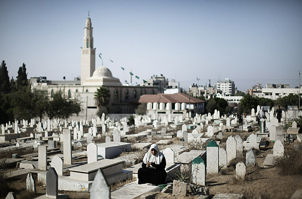 A Muslim woman prays at the grave of a relative early Friday morning in Gaza City.