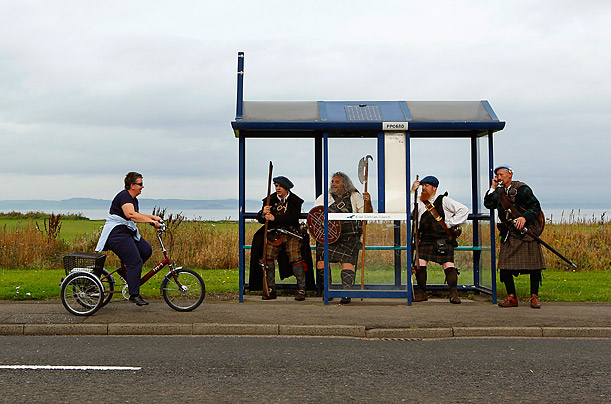 Jacobite Highlander re-enactors sit in a bus stop as a woman cycles past in Prestonpans,  Scotland.  The actors were in town promoting this weekends re–enactment of the 1754 Battle of Prestopans.