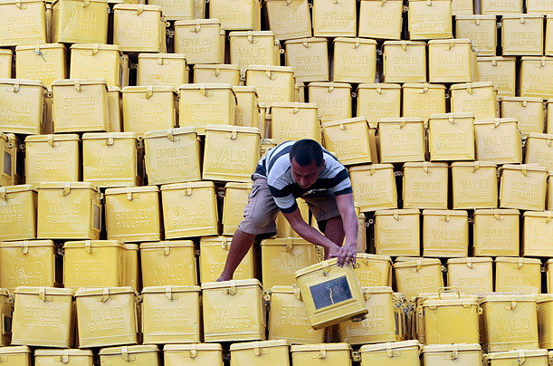 A worker arranges a pile of ballot boxes in preparation for the nationwide village elections in Manila, Phillipines.