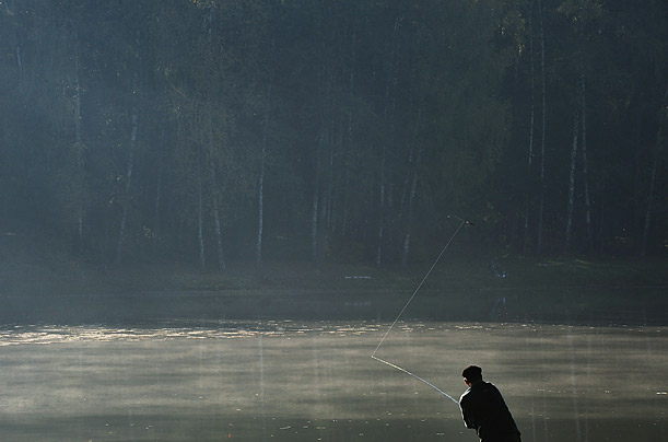 A man fishes in a pond in Moscow, Russia.