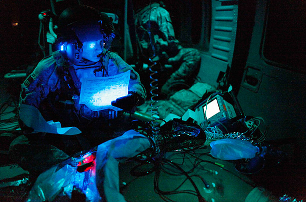 A U.S. flight medic examines a report on an unconscious U.S. serviceman during a night time emergency airlift in southern Afghanistan's Kandahar province.
