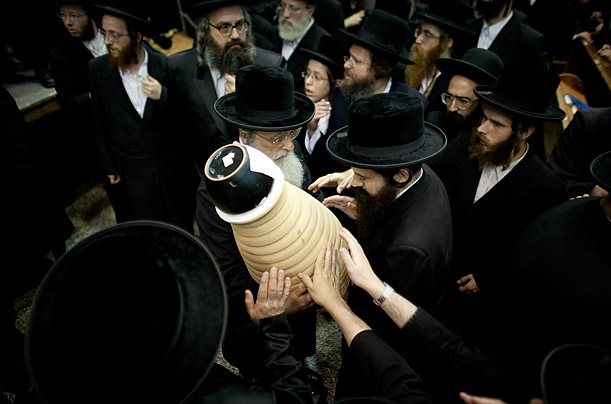 Ultra Orthodox Jewish men take part in a burial ceremony of the burnt remains of Torah scrolls in Bnei Brak, Israel.