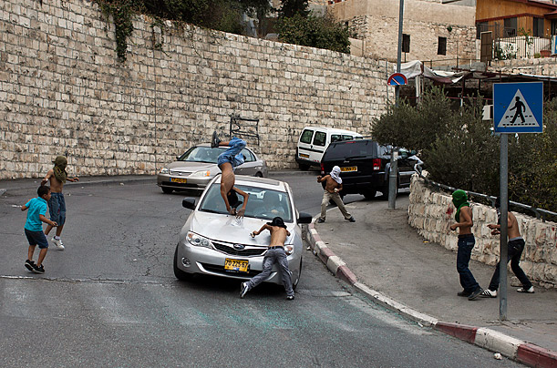 An Israeli motorist runs down a masked Palestinian youth who was standing among a group of youngsters throwing stones at Israeli cars in the mostly Arab east Jerusalem neighborhood of Silwan.