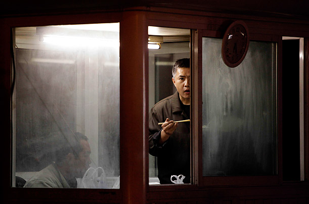 Security personnel eat as they watch over a entrance to the residential compound where Liu Xia, the wife of this year's Nobel Peace Prize winner Liu Xiaobo, is being held under house arrest in Beijing, China.