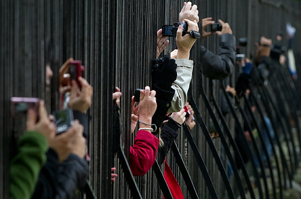 Members of the public take photos and videos through the barrier during the Changing of the Guard ceremony at Wellington Barracks in central London.