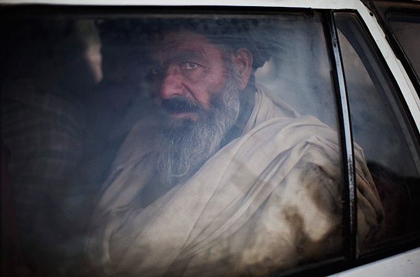 An Afghan looks from inside a car after being registered by Afghan National policemen and U.S. soldiers at a check point in Kandahar City, Afghanistan.
