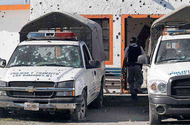 A policeman walks between patrol trucks riddled with bullet holes after a police station in Los Ramones, Mexico was attacked by gunmen. Six policemen survived the attack and resigned along with eight others, according to local media.