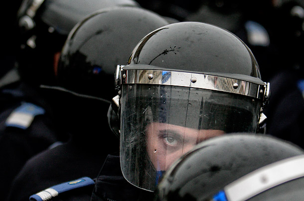 A riot police officer looks on during a protest against austerity measures in Bucharest, Romania.
