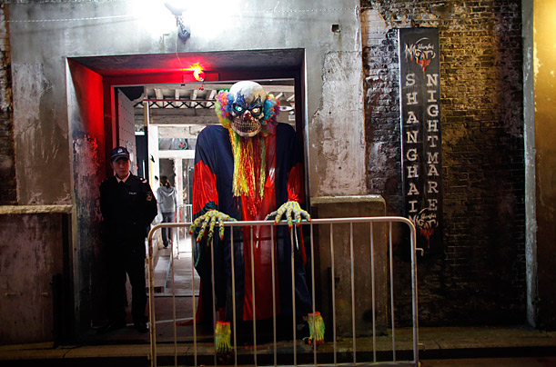 A costumed performer stands beside a security guard at the gate of China's first  haunted house attraction, the Shanghai Nightmare.
